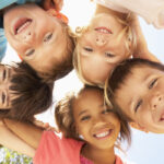 Looking up into a huddle of kids before they visit a pediatric dentist in San Antonio, TX