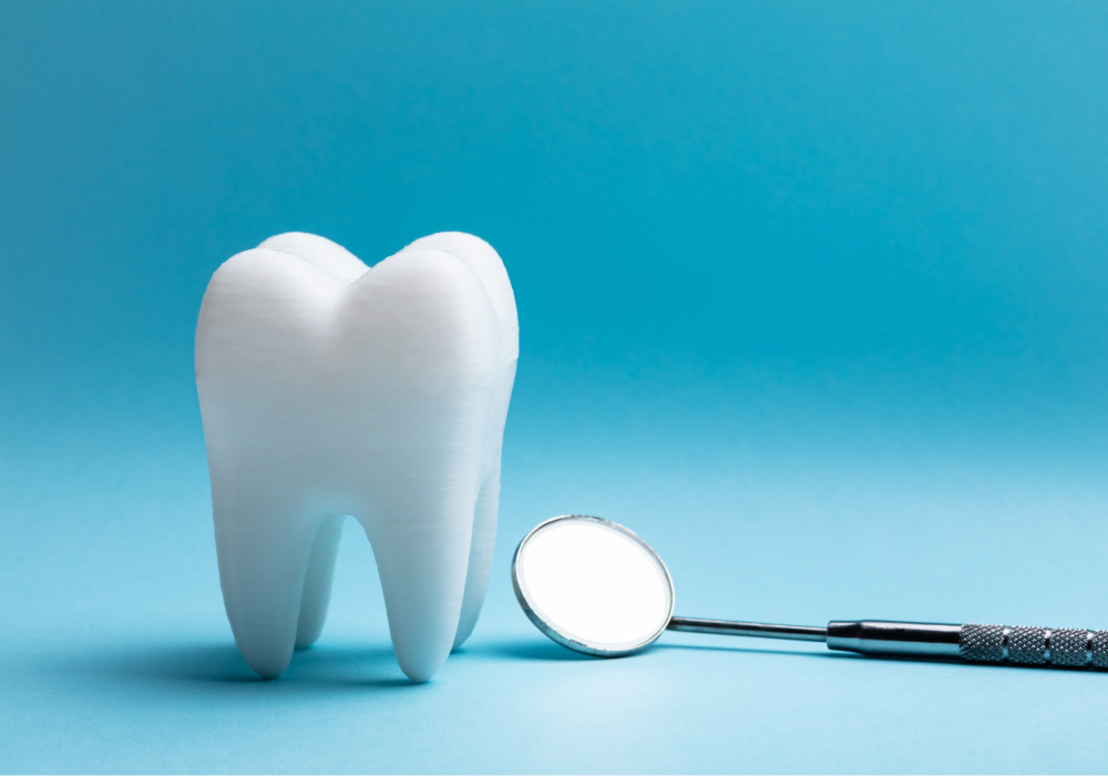 Closeup of a tooth next to a dental mirror against a blue background