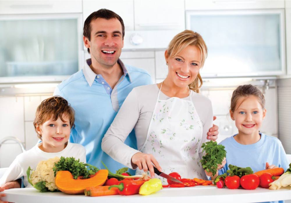 A family of four standing in front of a counter covered with foods that promote good oral health.