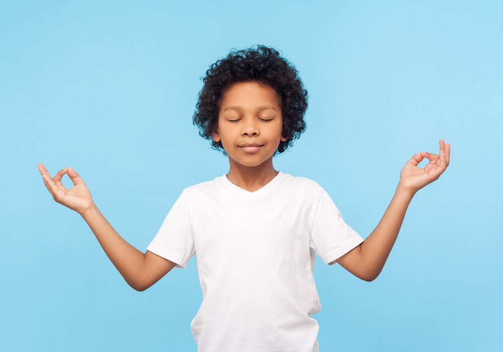 Boy in a white t-shirt in a ohm position on a blue background as he relaxes because of safe dental sedation at the dentist